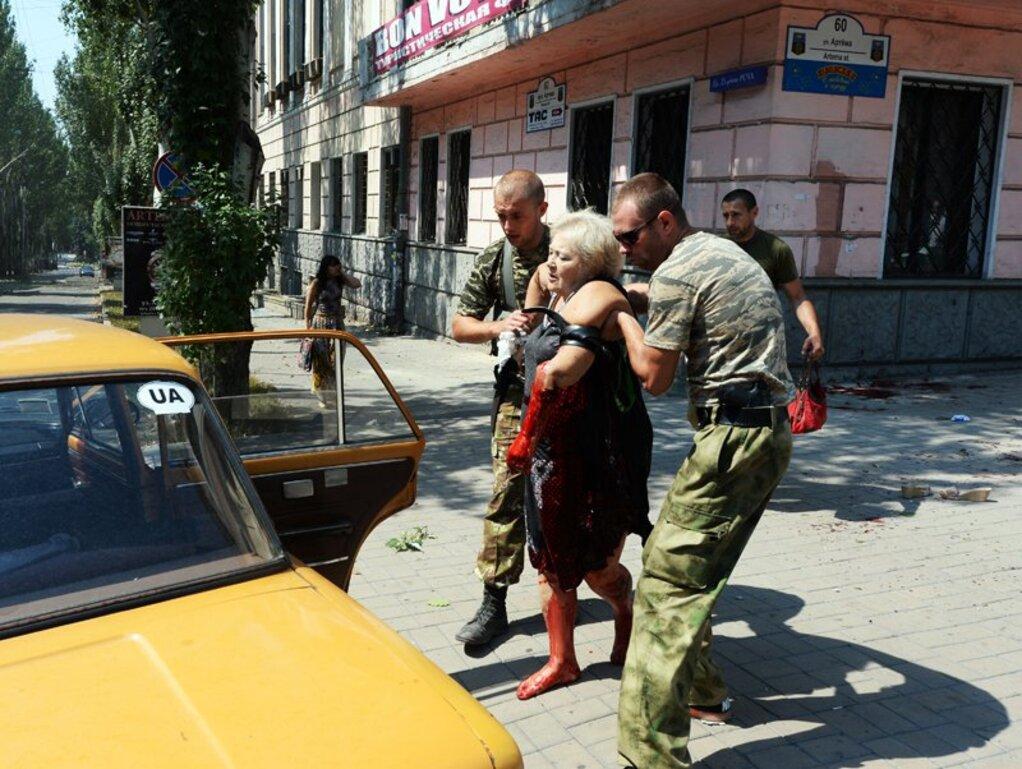 Bild 1/4: Fotograf Mikhail Voskresenskiy hielt kurz nach dem Angriff auf den Stadtkern dramatische Szenen fest: Hier eine schwer verwundete Frau, die von zwei Soldaten der prorussischen Volkswehr zu einem Wagen gebracht wird.